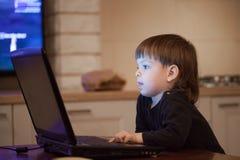 Niño pequeño que se sienta en el ordenador portátil y las prensas el botón El niño de pelo largo incluye historietas Foto de archivo