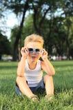 Niño pequeño que se sienta en el parque Foto de archivo