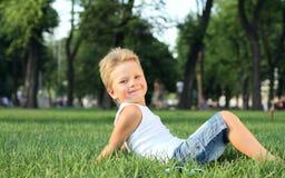 Niño pequeño que se sienta en el parque Fotos de archivo libres de regalías