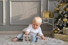 Niño pequeño que se sienta en el piso y que juega cerca del árbol de navidad Fotos de archivo libres de regalías