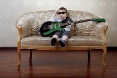 Niño pequeño que se sienta en el sofá atractivo Imagenes de archivo