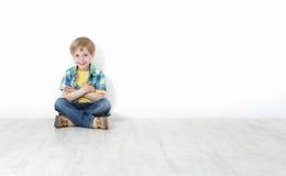 Niño pequeño que se sienta en el suelo que se inclina contra la pared Imagen de archivo libre de regalías