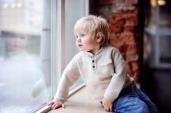 Niño pequeño que se sienta en el travesaño de la ventana y que mira la ventana fotos de archivo libres de regalías