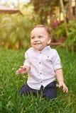 Niño pequeño que se sienta en hierba imagen de archivo libre de regalías