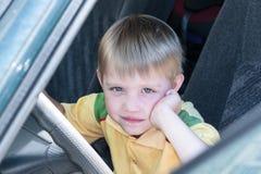Niño pequeño que se sienta en la conducción de automóviles Una mano apoya su mejilla Imágenes de archivo libres de regalías