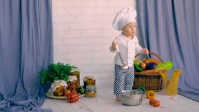 Niño pequeño que se sienta en la decoración de la cocina y que cocina con la verdura