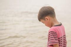 Niño pequeño que se sienta en la roca en la mirada de la cara de la playa feliz Fotos de archivo libres de regalías