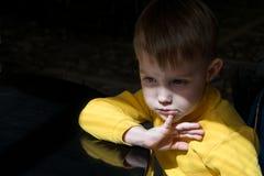 Niño pequeño que se sienta en la tabla en un estado pensativo Foto de archivo libre de regalías