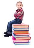 Niño pequeño que se sienta en los libros coloridos apilados Imagen de archivo