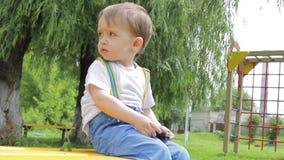 Niño pequeño que se sienta en un banco en el patio, jugando con el teléfono elegante metrajes