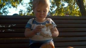 Niño pequeño que se sienta en un banco y que come el bollo almacen de video