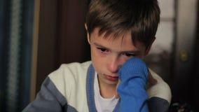 Niño pequeño que se sienta en un escritorio que llora, rasgones en el suyo metrajes