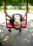 Niño pequeño que se sienta en un oscilación Fotografía de archivo