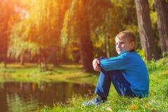 Niño pequeño que se sienta en una hierba cerca del lago Fotos de archivo