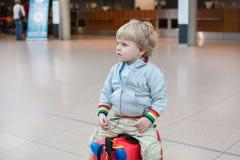 Niño pequeño que se sienta en una maleta en el aeropuerto Fotos de archivo