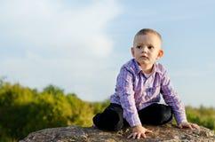 Niño pequeño que se sienta en una roca Foto de archivo