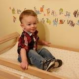 Niño pequeño que se sienta en una tabla cambiante Foto de archivo libre de regalías