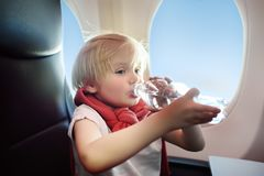 Niño pequeño que se sienta por la ventana de los aviones durante el vuelo Imagenes de archivo