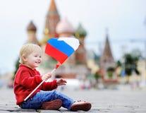 Niño pequeño que se sienta y que juega con la bandera rusa Imágenes de archivo libres de regalías