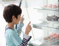 Niño pequeño que selecciona la torta en la tienda de la panadería imagenes de archivo