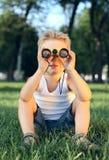 Niño pequeño que sienta en el parque con los prismáticos Imagen de archivo