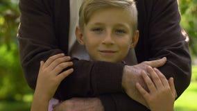 Niño pequeño que sonríe en cámara, abuelo que abraza al niño, confianza y concepto del cuidado almacen de metraje de vídeo