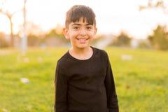 Niño pequeño que sonríe en el parque Imagenes de archivo
