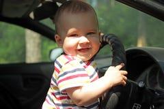 Niño pequeño que sonríe sosteniendo la rueda del coche foto de archivo