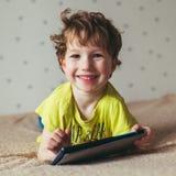 Niño pequeño que sonríe y que mira la tableta, usando tecnología moderna Foto cuadrada imágenes de archivo libres de regalías