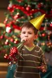 Niño pequeño que sopla el claxon del Año Nuevo Foto de archivo