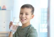 Niño pequeño que sostiene el vidrio de agua dulce imagen de archivo