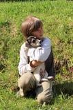 Niño pequeño que sostiene un perrito Imagen de archivo libre de regalías