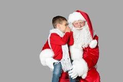 Niño pequeño que susurra en oído auténtico del ` de Santa Claus fotografía de archivo libre de regalías