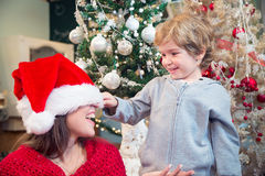 Niño pequeño que tira del sombrero de Santas en ojos de las madres Fotografía de archivo