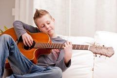 Niño pequeño que toca la guitarra en casa Fotos de archivo libres de regalías