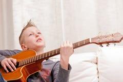 Niño pequeño que toca la guitarra en casa Imagen de archivo