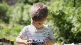 Niño pequeño que toma las fotos en la cámara del vintage almacen de video
