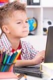 Niño pequeño que trabaja en el ordenador portátil Fotografía de archivo libre de regalías