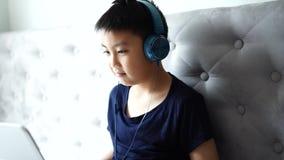 Niño pequeño que usa el juego del juego del ordenador portátil en casa para relajarse almacen de metraje de vídeo