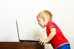 Niño pequeño que usa el ordenador de la PC del ordenador portátil en casa Imagen de archivo