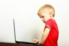 Niño pequeño que usa el ordenador de la PC del ordenador portátil en casa Fotografía de archivo libre de regalías