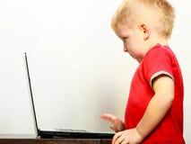 Niño pequeño que usa el ordenador de la PC del ordenador portátil en casa Imagen de archivo libre de regalías