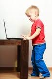 Niño pequeño que usa el ordenador de la PC del ordenador portátil en casa Foto de archivo libre de regalías