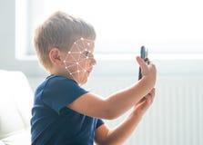 Niño pequeño que usa la autentificación de la identificación de la cara Niño con un smartphone Concepto nativo de los niños de Di fotografía de archivo libre de regalías