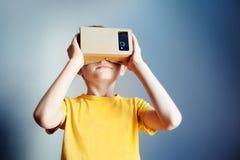 Niño pequeño que usa nuevas auriculares de la realidad virtual fotografía de archivo