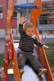 Niño pequeño que va abajo del metal y de la grada de madera Foto de archivo