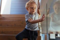 Niño pequeño que viene abajo escaleras Foto de archivo libre de regalías