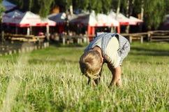 Niño pequeño rubio lindo que juega en un parque herboso Imagen de archivo