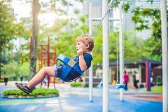 Niño pequeño rubio precioso en un oscilación en el parque Muchacho adorable que se divierte en el patio Fotos de archivo libres de regalías