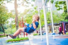 Niño pequeño rubio precioso en un oscilación en el parque Muchacho adorable que se divierte en el patio Fotografía de archivo libre de regalías